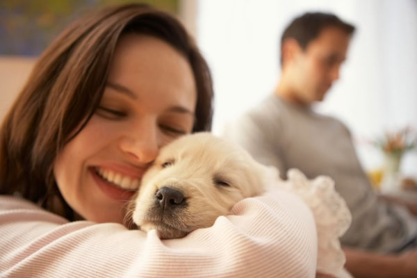 Woman snuggling with a puppy