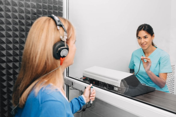 Audiologist conducting pure tone test on a patient