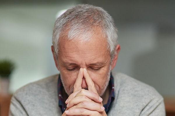 Man holding the bridge of his nose